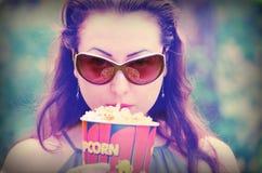 Jolie fille mangeant du maïs éclaté Images libres de droits
