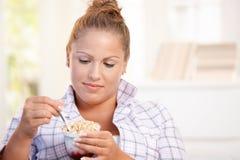 Jolie fille mangeant du yaourt à la maison suivant un régime Images libres de droits