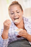 Jolie fille mangeant du yaourt à la maison suivant un régime le sourire Photographie stock libre de droits