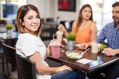 Jolie fille mangeant le déjeuner avec quelques amis Photo stock