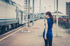 Jolie fille marchant le long des voies Images stock