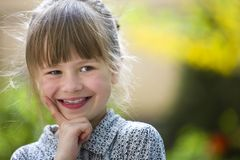 Jolie fille mignonne d'enfant avec les yeux gris et les cheveux justes souriant in camera dehors sur le vert ensoleill? brouill?  images stock