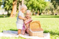 Jolie fille montrant un carnet à un petit garçon photos libres de droits