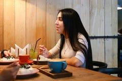 Jolie fille parlant, écoutant, mangeant et souriant à la table dans c Photographie stock