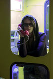 Jolie fille parlant par la cabine téléphonique dans la cabine téléphonique Image libre de droits
