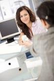Jolie fille passant le téléphone au collègue dans le bureau Photographie stock libre de droits