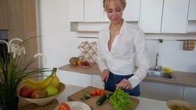 Jolie fille préparant la salade des légumes frais sur la planche à découper dans la cuisine moderne clips vidéos