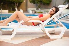 Jolie fille prenant un bain de soleil par la piscine Photo stock