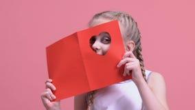 Jolie fille regardant par le coeur dans la carte de Valentine, ayant l'amusement en vacances banque de vidéos