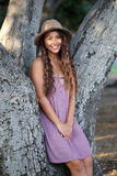 Jolie fille reposant l'escroc d'un arbre Photo libre de droits