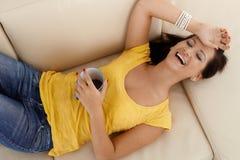 Jolie fille riante s'étendant sur le sofa Photo libre de droits