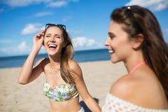 Jolie fille riante s'asseyant sur la plage avec l'ami Image stock