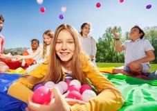 Jolie fille s'étendant sur le tapis avec une bracée de boules Image libre de droits