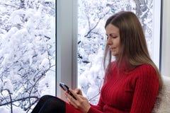 Jolie fille s'asseyant sur le rebord de fenêtre utilisant le smartphone L'hiver à l'extérieur photos libres de droits