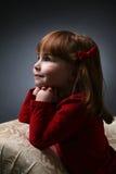 Jolie fille se mettant à genoux sur le divan avec le menton sur des mains photographie stock