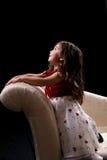 Jolie fille se mettant à genoux sur le divan et recherchant photographie stock libre de droits