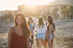 Jolie fille se tenant sur la plage avec le groupe d'amis Images libres de droits