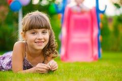 Jolie fille se trouvant sur l'herbe au terrain de jeu photo stock