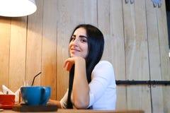 Jolie fille souriant, posant et regardant in camera la table dans la Co Image libre de droits