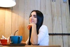 Jolie fille souriant, posant et regardant in camera la table dans la Co Photos libres de droits