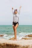 Jolie fille sur la grande pierre à la plage Photos libres de droits