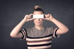 Jolie fille tenant le papier vide de l'espace de copie à ses yeux Photographie stock libre de droits