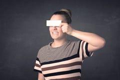 Jolie fille tenant le papier vide de l'espace de copie à ses yeux Photo libre de droits