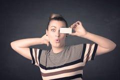 Jolie fille tenant le papier vide de l'espace de copie à ses yeux Images libres de droits