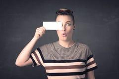 Jolie fille tenant le papier vide de l'espace de copie à ses yeux Photographie stock
