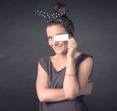 Jolie fille tenant le papier vide de l'espace de copie à ses yeux Image libre de droits