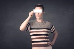 Jolie fille tenant le papier vide de l'espace de copie à ses yeux Images stock