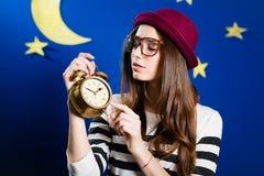 Jolie fille tenant le réveil sur des étoiles de papier et Photo libre de droits