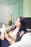 Jolie fille vérifiant le wishlist avec le stylo sur brouillé Photo stock