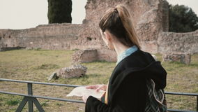 Jolie fille visitant le plancher inférieur de Domus Augustana pendant son voyage à Rome, Italie La femme regarde la carte banque de vidéos