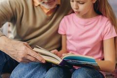 Jolie histoire de lecture d'enfant avec le grand-parent Image libre de droits