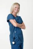 Jolie infirmière avec le sourire croisé par bras photographie stock libre de droits