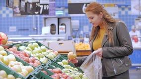 Jolie jeune et belle femme aux cheveux rouges achète de la nourriture, des fruits, des pommes sur le marché, au supermarché La fi banque de vidéos