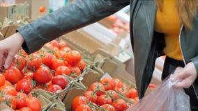 Jolie jeune et belle femme aux cheveux rouges achète de la nourriture, des fruits, des tomates sur le marché, au supermarché La f clips vidéos