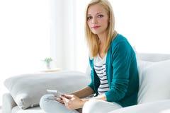 Jolie jeune femme à l'aide de son comprimé numérique à la maison Image libre de droits