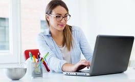 Jolie jeune femme à l'aide de son ordinateur portable dans le bureau Photos libres de droits
