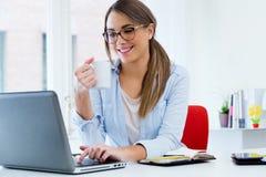 Jolie jeune femme à l'aide de son ordinateur portable dans le bureau Photos stock