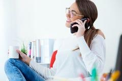 Jolie jeune femme à l'aide de son téléphone portable dans le bureau Images stock