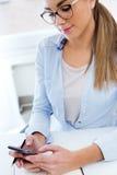 Jolie jeune femme à l'aide de son téléphone portable dans le bureau Image stock