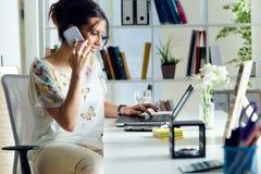 Jolie jeune femme à l'aide de son téléphone portable dans le bureau Photographie stock libre de droits