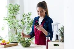 Jolie jeune femme à l'aide de son téléphone portable tout en préparant la salade dans la cuisine à la maison photo stock