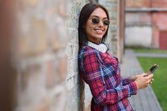 Jolie jeune femme à l'aide du smartphone Photographie stock libre de droits
