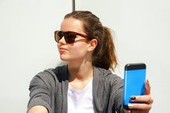 Jolie jeune femme à l'aide du téléphone portable au-dessus du mur blanc Photographie stock libre de droits