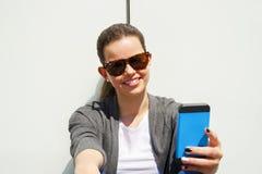 Jolie jeune femme à l'aide du téléphone portable au-dessus du mur blanc Photo stock