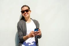 Jolie jeune femme à l'aide du téléphone portable au-dessus du mur blanc Images libres de droits