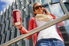 Jolie jeune femme à l'aide du téléphone portable tenant la tasse de coffe Photo stock